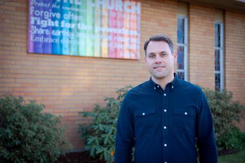 Pastor Adam Hange by church banner
